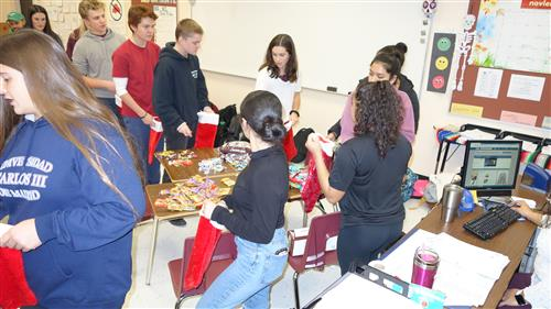Students create assembly line in stuffing holiday stockings for miliary alumnus