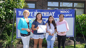 Barbara Beckett with three of her students whose art was selected as part of the MDCC at journal
