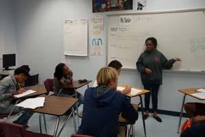 RBR sophomore Tanita Waddy works out an English question with the guidance of seniors Aniyah Massie