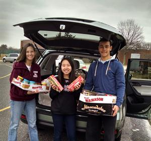 English teacher Cassandra Dorn and  Hayley Rienzo, and Derrick Bradley loading food drive truck